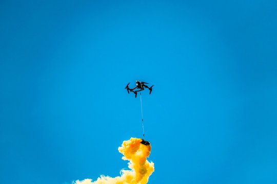 Black drone in the blue sky with a yellow smoke bomb