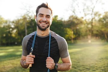 Handsome young strong sports man posing outdoors at the nature park location with skipping rope. Fotomurales