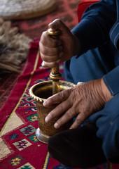 Saudi man preparing coffe with a pestle in a majlis, Asir province, Tanomah, Saudi Arabia