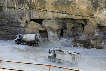 Trucks pass by caves at the ancient town of Hasankeyf by the Tigris river, which will be significantly submerged by the Ilisu dam being constructed, in southeastern Turkey
