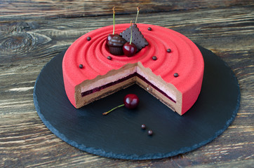 Part of contemporary cherry mousse cake covered with red velvet spray, decorated with chocolate elements and fresh cherries on black plate on wooden background