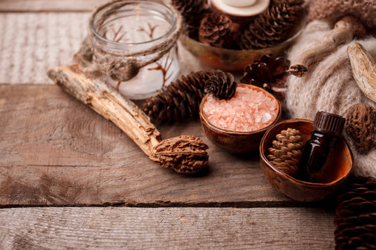 Wood scents for winter time aromatherapy. Pine cones, candles, essential oil bottles, top view. Spa relax winter concept, copy space