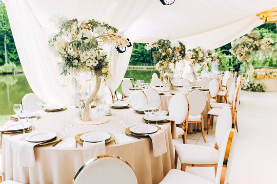 Wedding in a white tent by the lake. Beautiful flowers. luxurious wedding decor in white.