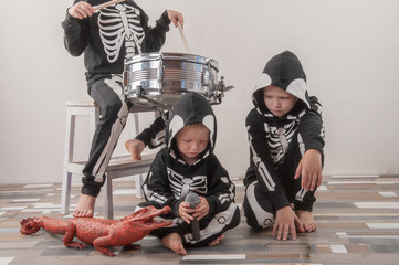 Happy friendly family of musicians in carnival costumes, boys and young mother play drum and try to sing with microphone. Black suit with image of skeletons. Classic halloween costume. Funny children Wall mural