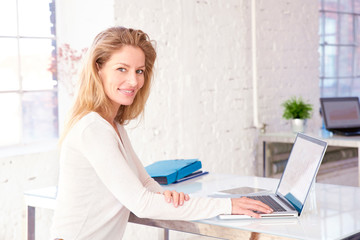 Confident businesswoman sitting at office desk and working on financial plan