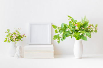 Home interior with decor elements. White frame, branches with green leaves in a vase, interior decoration