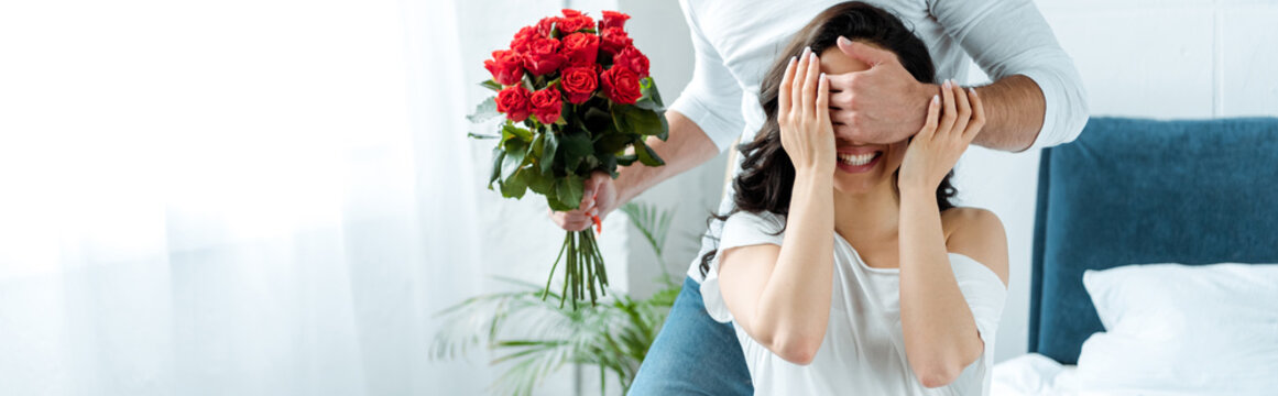partial view of man with bouquet of red roses closing woman eyes to make surprise in bedroom