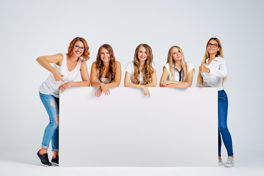 Advertising. Your text here. Group of pretty young women holding an empty board with copy space together on white background.