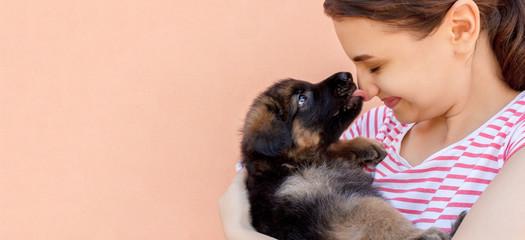 cute German shepherd puppy kissing woman's nose