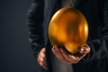 Successful businesswoman holding golden egg