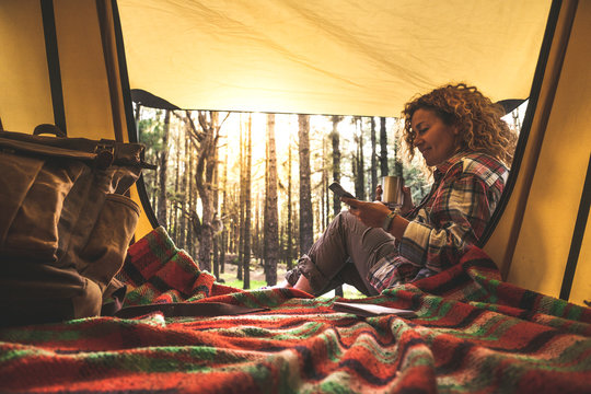 Cheerful happy people caucasian woman use cellular phone sitting outside a tent in the forest with sunlight in background - alternative travel vacation concept for independent adult with technology