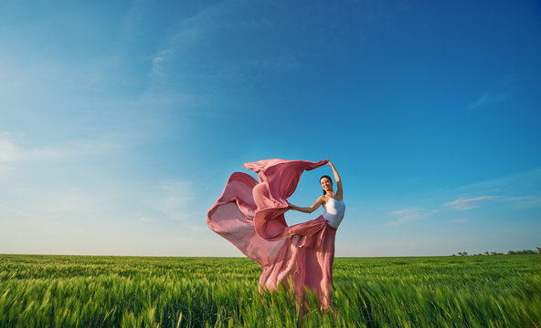 Classic dance on nature background. Professional female modern dancer in pink fabric dress dancing in green field.