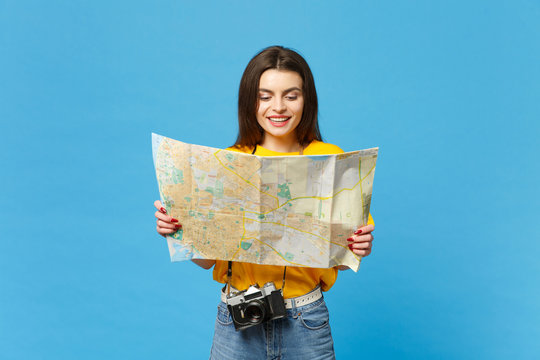 Portrait of cheerful young woman in vivid casual clothes with retro vintage photo camera hold paper city map isolated on blue wall background in studio. People lifestyle concept. Mock up copy space.
