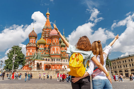 Two happy young happy girls travels in Russia and taking selfie in front of the St Basil Cathedral