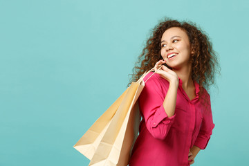 Pretty african girl in pink casual clothes holding package bag with purchases after shopping isolated on blue turquoise wall background. People sincere emotions lifestyle concept. Mock up copy space.