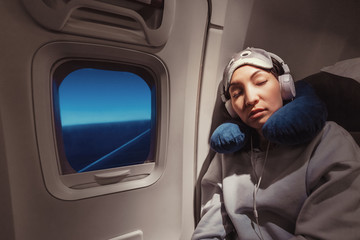 Asian girl sleeping in her seat on the plane near the window in a mask and with a pillow to sleep. The concept of travel with comfort and jetlag