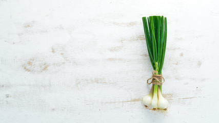 Green onion on a white wooden background. Top view. Free space for text. Wall mural