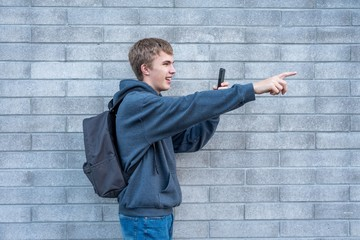 Teenager pointing to something he is recording with his cellphone.