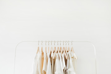 Minimal fashion clothes concept. Female blouses and t-shirts on hanger on white background. Fashion blog, website, social media hero header template. Wall mural