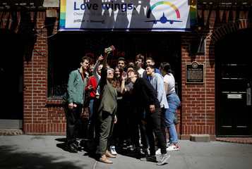 Students pose for a selfie photograph outside the Stonewall Inn, site of the1969 Stonewall uprising in New York