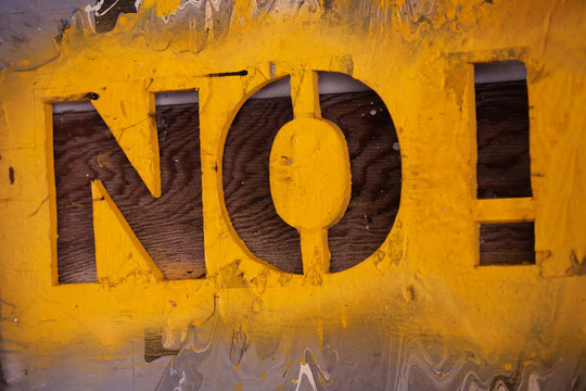 Stencil font signage with many layers of paint and textures with the words No! and yellow spray paint.