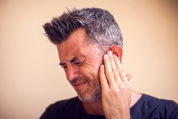 Man feels ear pain isolated. People, healthcare and medicine concept Wall mural
