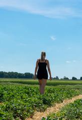 Junge Frau läuft durch ein Erdbeerfeld. Standort: Deutschland, Nordrhein-Westfalen, Heiden