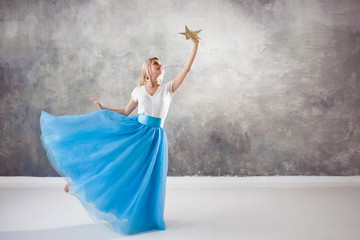 girl reaches for her dream, a concept. Young beautiful woman holding a star Wall mural