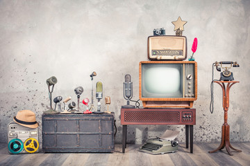 Retro TV, old studio microphones, outdated broadcast radio, journalist's reel tape recorder, aged telephone, film camera, golden award star, quill, typewriter. Journalism concept. Vintage style photo
