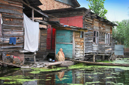 Traditional kashmiri view,  old wooden houses on stilts, boat, Dal lake with duckweed, hanging laundry in Srinagar, Jammu & Kashmir, Northern India. Local people spend all their life on the water.