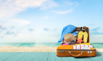 Obraz Retro suitcase with travel objects  on sea background - fototapety do salonu