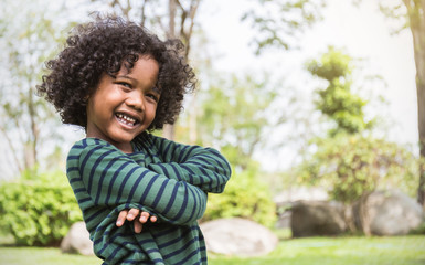 Fun in the spring park. Portrait of young happy black boy stand on green grass background. Education back to school spend leisure time in nature forest concept Fototapete