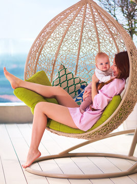 happy young woman enjoying maternity, sitting in the swing on summer patio
