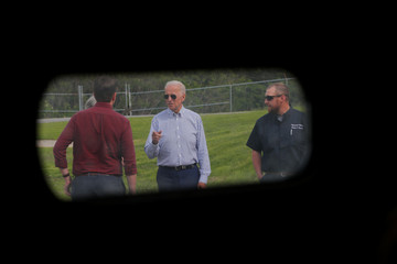 A garage door window frames Democratic 2020 U.S. presidential candidate Biden as he tours the Plymouth Area Renewable Energy Initiative in Plymouth