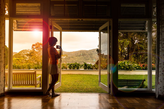 Woman admiring natural scenic sunrise from home interior with coffee