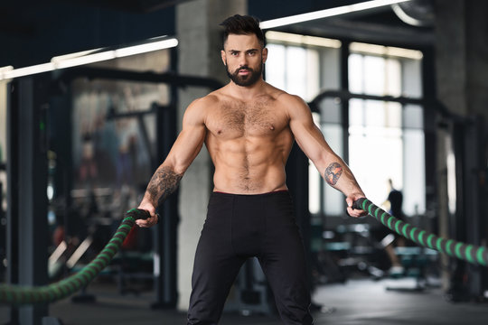 Muscular guy with naked torso exercising with battle ropes