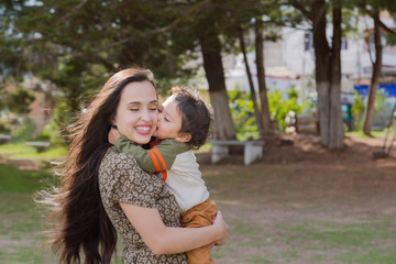 Cute two year old boy kissing his young mother while they both smile and have fun