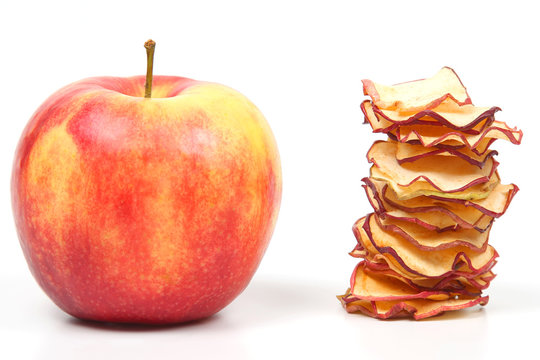 Fresh Apple and a stack of dried Apple slices on white background