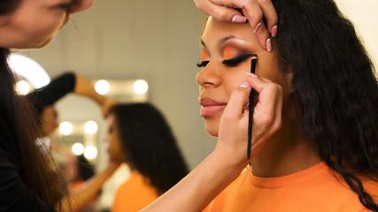 Makeup artist draws arrows on eyelids of african girl. Evening make-up. Closeup portrait side view Wall mural