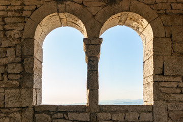 Two windows in an old tower or fortress, view from the inside.
