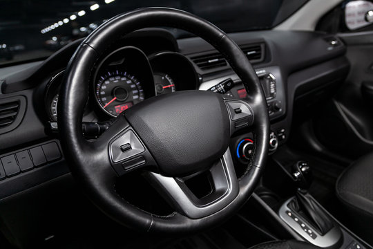 Close-up of the dashboard, speedometer, tachometer and steering wheel with phone setting and volume buttons. Luxurious car interior details.