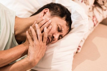 TMD and TMJ healthcare concept: Temporomandibular Joint and Muscle Disorder. Asia man hand on cheek face as suffering from facial pain, mumps or toothache