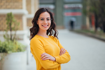 Obraz Portrait of a young confident woman outdoors, smiling at camera. - fototapety do salonu