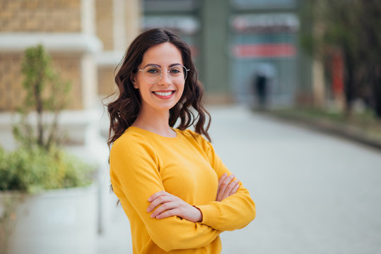 Portrait of a young confident woman outdoors, smiling at camera.