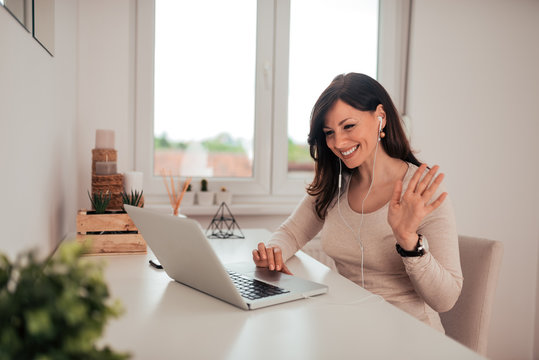 Portrait of a charming smiling woman having video calll on laptop.
