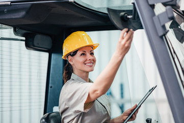 Beautiful woman operating forklift truck at the factory.
