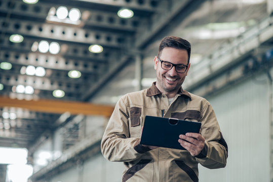 Portrait of a smiling factory engineer, low angle image. Handsome man looking at tablet while working at industrial building.