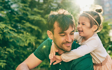 Outdoor image of happy cute little girl smiling and playing with her father. Handsome dad and pretty kid having fun and playing at playground. Daddy and daughter shares love together. Fatherhood Fototapete