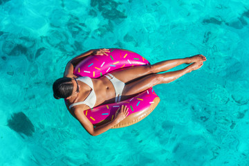 Beach vacation woman relaxing in donut inflatable float floating on ocean in Caribbean travel summer getaway. Girl in white bikini top view.