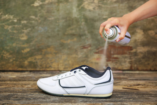 Female hand holding a spray deodorant for shoes.